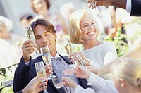 Wedding guests toasting to bride and groom, outdoors