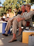 Senior couple sitting on bench on sidewalk