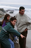Father with two daughters  (8-9), (12-13), standing on rocky beach