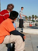 Two teenage boys (16-17) looking at skateboarder on promenade