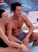 Young couple sitting on side of jacuzzi