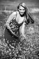Mid adult women picking flowers in field, smiling, portrait (B&W)