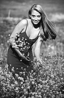 Mid adult women picking flowers in field, smiling, portrait (B&W)