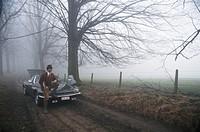 Businessman sitting on car bonnet with rifle, mist