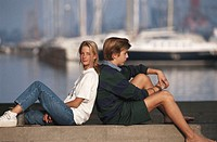 Teenage girl and boy (16-17) sitting back to back by harbour