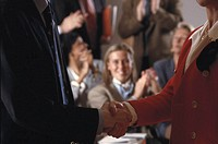 Businessman and woman shaking hands,  mid-section, colleagues in background