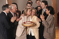 Woman holding birthday cake by co-workers in office