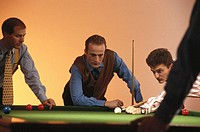 Three businessmen playing billiards