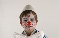 Boy (4-5) dressed up as clown, close-up