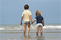 Boy and girl (3-5) holding hands on beach, rear view