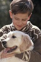 Boy (8-11) holding dog outdoors