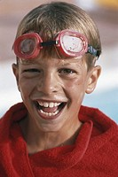 Boy (8-11) wearing swimming goggles, close-up, portrait
