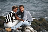 Mid adult couple sitting on rocks by beach