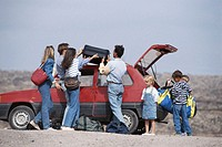 Family loading luggage and suitcase in car