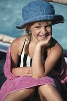 Girl (6-7) sitting with hand on chin poolside, portrait