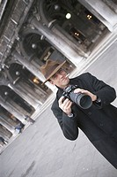 Mid adult man holding camera, outdoors