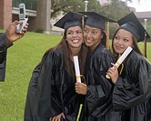Man photographing three young female graduates with camera phone