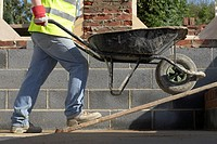Workman pushing wheelbarrow up ramp, low section