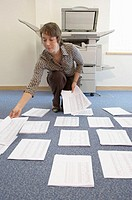 Woman laying out papers on floor by photocopier