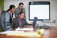 Two businessmen with a businesswoman looking at a laptop