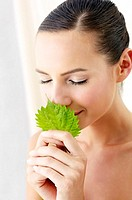 Woman smelling a green leaf