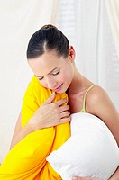 Woman hugging two pillows