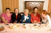 Five mature women sitting at table drinking wine, laughing