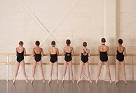 Seven ballerina girls (11-13) standing on toes, rear view