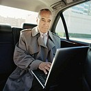 Mature businessman working on laptop in car