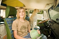 Teenage boy (13-15) with skateboard sitting in van with dog, portrait