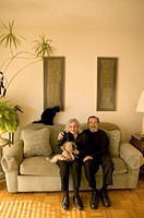 Senior man and woman sitting on sofa with cats, smiling, portrait