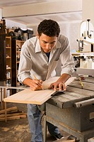 Man drawing pencil line on wood in wood shop