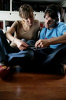 Young couple looking at CD covers, man wearing headphones