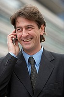 Businessman using mobile phone, smiling, close-up