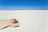 Mature man lying on white gypsum sand, side view