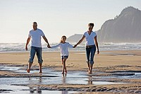 Family walking on sand at beach
