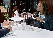 Businesswoman handing papers to man in restaurant