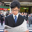 Young adult businessman reading newspaper