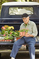 Portrait of elderly man sitting on tailgate with flowers