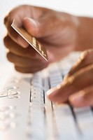 Close up of hands typing on keyboard and holding credit card