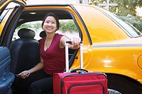 Young woman with suitcase inside a cab