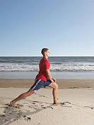 Man stretching in sand at beach