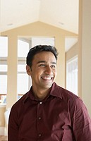 Man standing in house smiling