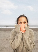 Woman in sweater drinking coffee at beach