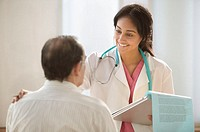 Female doctor talking to patient while holding clipboard