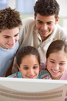 Four teenagers in front of computer looking at screen