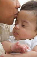 Close up of mother kissing sleeping baby on forehead