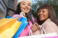 Two African American women smiling with shopping bags