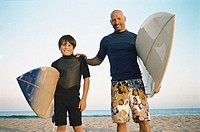 Father and son posing with surfboards