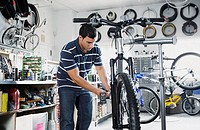 Man repairing bike in bike shop